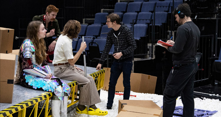 A graduate director gives notes to a cast of actors.